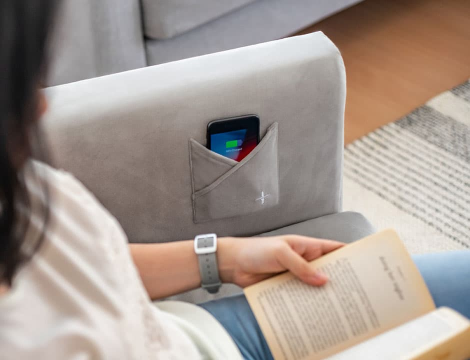 lady reading book on IKEA Koarp covered in velvet sofa cover slipcover with wireless charger pocket