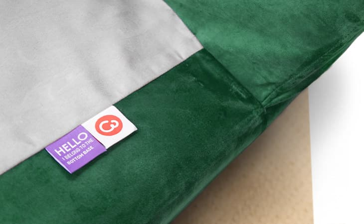 Close-up of custom sofa cover labels, made by Comfort Works in green velvet (Rouge Emerald).
