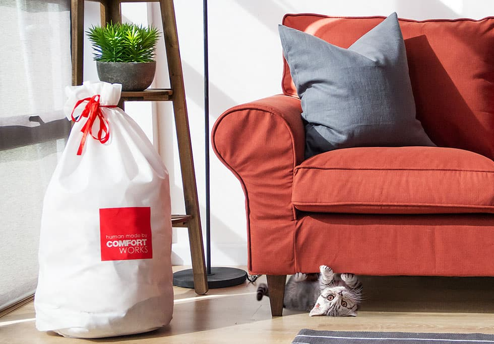 IKEA Ektorp 3 seater with custom sofa covers in wool, next to a Comfort Works delivery bag and comfort cat.