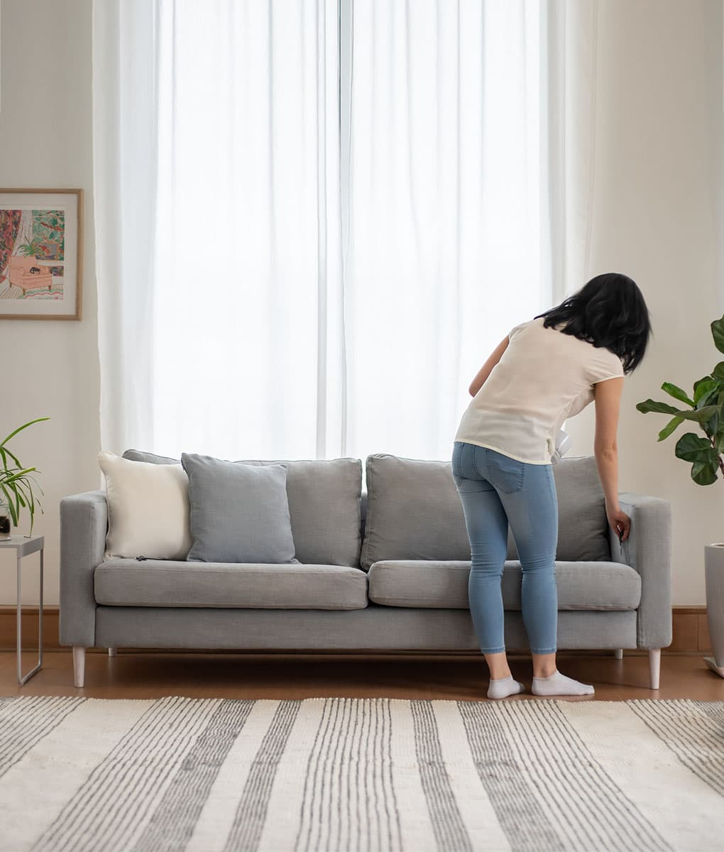 lady charging phone on wireless charging built in on ikea karlstad 3 seater sofa covered in madison ash panama cotton sofa cover slipcover
