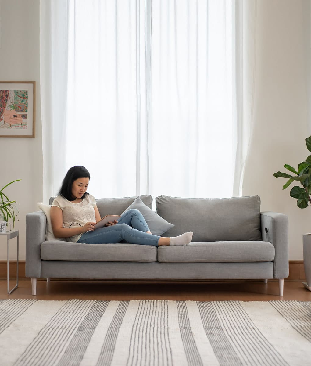lady chilling and playing ipad on ikea karlstad 3 seater sofa covered in madison ash panama cotton sofa cover slipcover