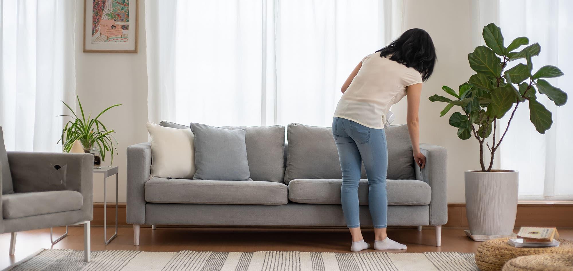Joven cargando su móvil usando cargador inalámbrico en sofá Karlstad de 3 plazas de IKEA con fundas de sofá en Madison Ash Algodón Panamá