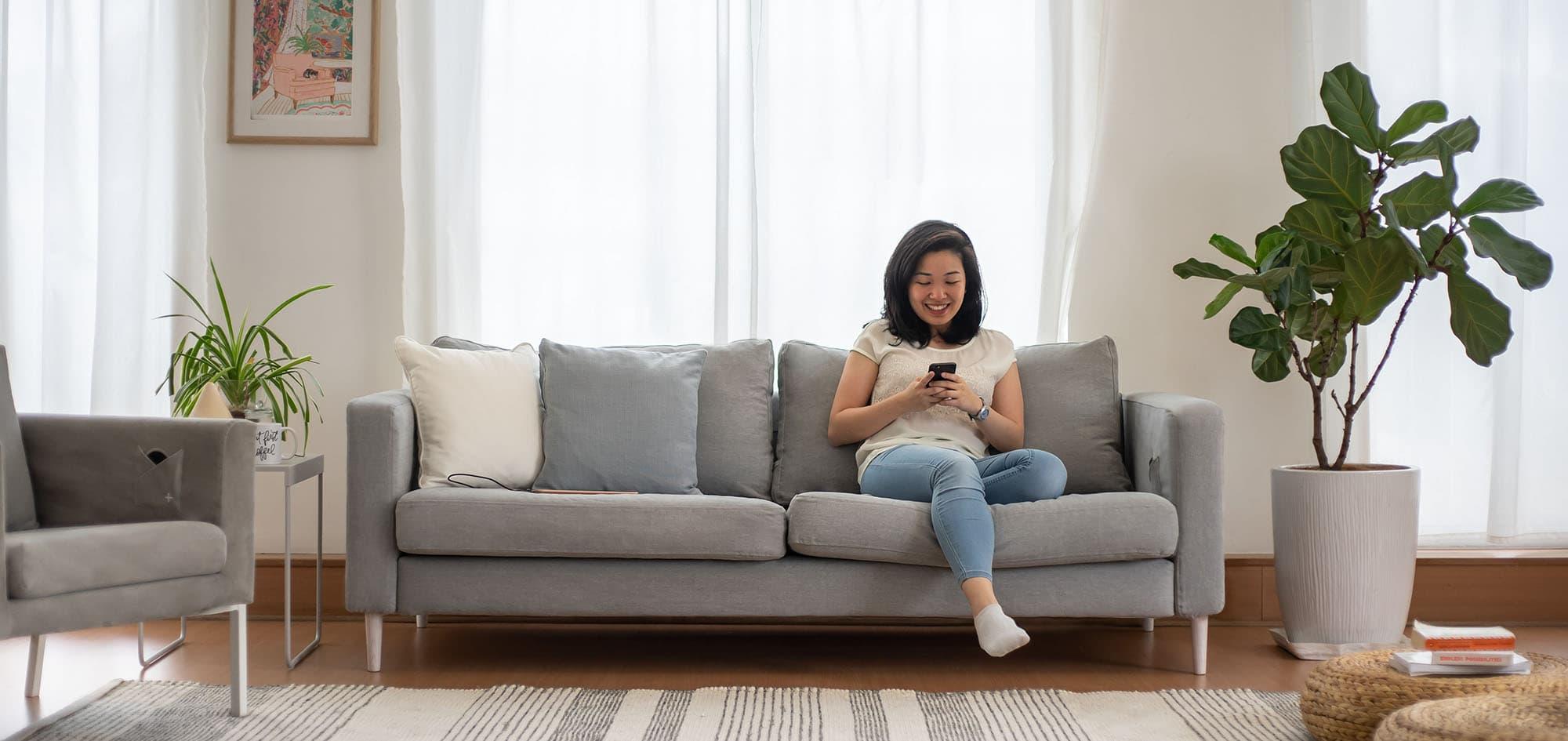 Joven relajándose jugando con su móvil en un sofá Karlstad de 3 plazas de IKEA con fundas de sofá en Madison Ash Algodón Panamá