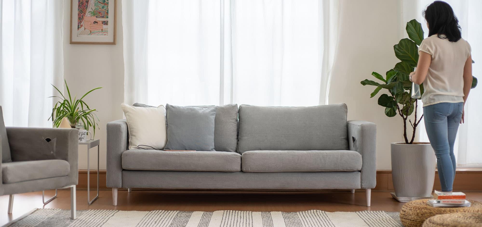 Joven regando plantas esperando que su móvil esté cargado en sofá Karlstad de 3 plazas de IKEA con fundas de sofá en Madison Ash Algodón Panamá