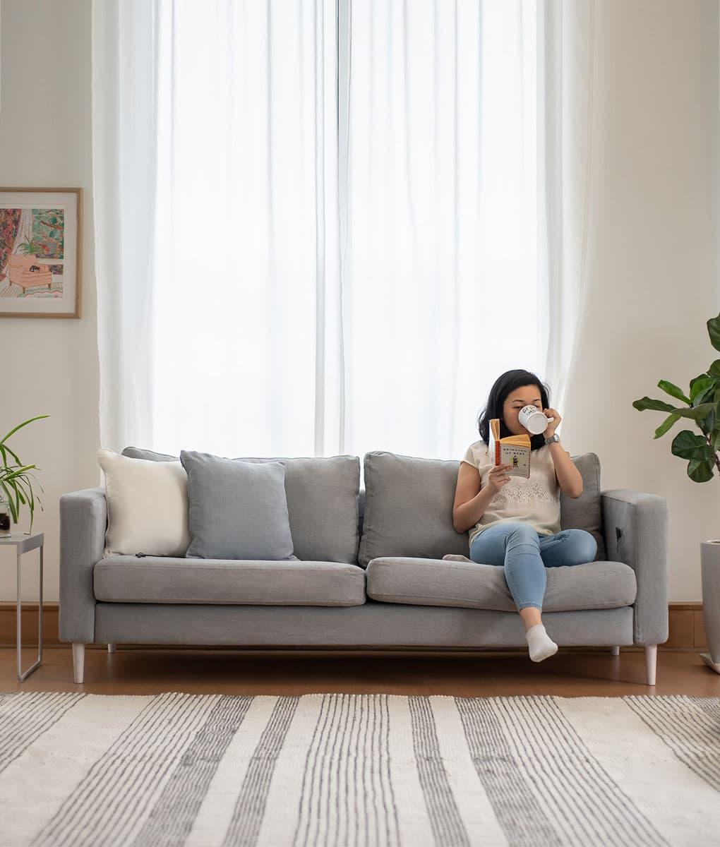 Joven relajándose leyendo un libro en un sofá Karlstad de 3 plazas de IKEA con fundas de sofá en Madison Ash Algodón Panamá